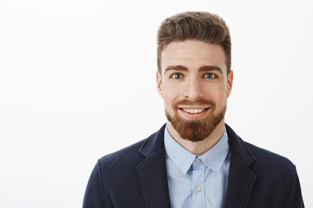 수염과 큰 파란 눈을 가진 야심 찬 잘 생기고 젊은 세련된 성숙한 남성은 회색 벽을 통해 기회 쇼 기술을 기다리고 회색 벽을 통해 트렌디 한 정장에 흥분하고 기쁘게 미소 서 미소 무료 사진