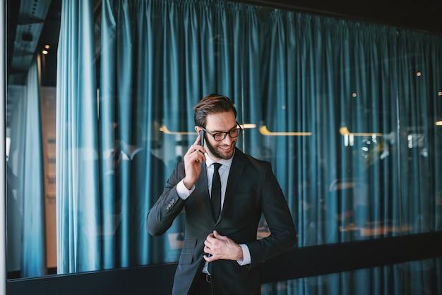 野心的なハンサムな笑みを浮かべて白人ひげを生やしたフォーマルな服装と眼鏡のビジネスコール。本社のインテリア。 Premium写真