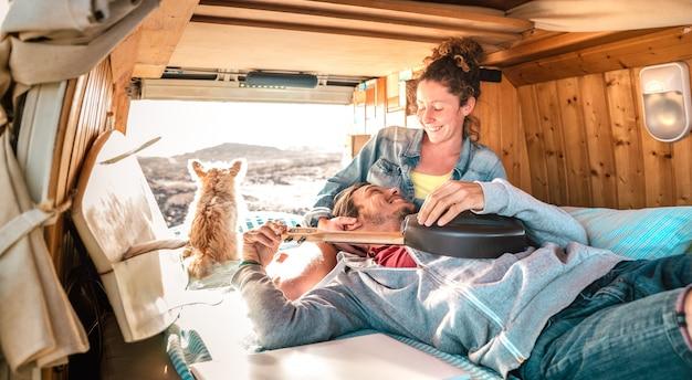 ヒッピーカップルamd犬の夕暮れ時のビンテージバン輸送で一緒に旅行 Premium写真