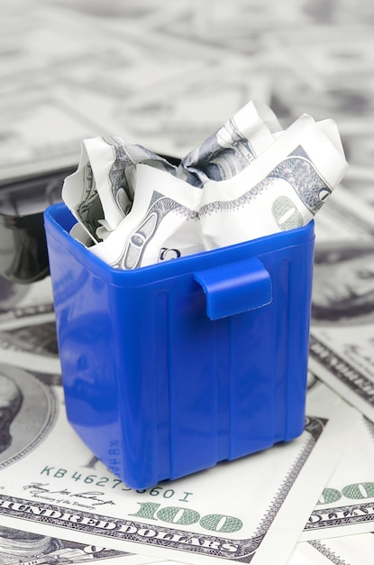 American cash notes are thrown into the trash bin on a multitude of hundred dollar bills Premium Photo