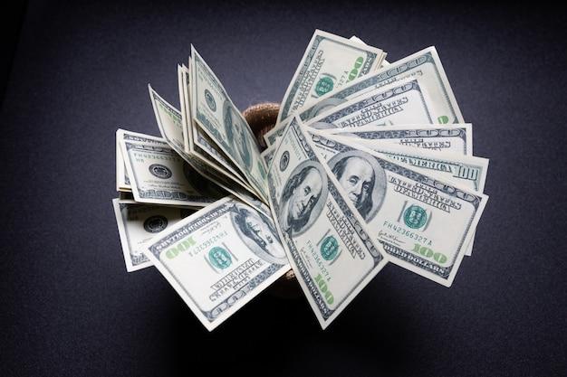 어두운 방에 검은 테이블에 자루에 미국 달러 현금 돈 무료 사진