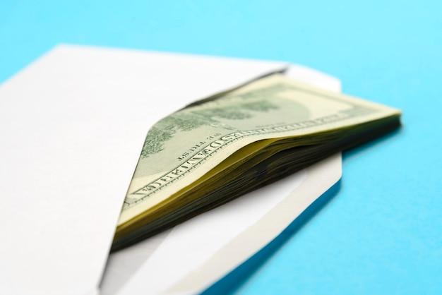 American dollars in open white postal envelope on blue Premium Photo