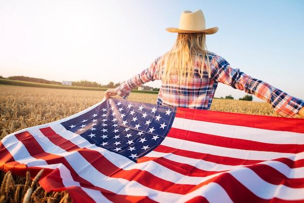 Американская женщина-фермер в повседневной одежде с распростертыми руками держит флаг сша на пшеничном поле Бесплатные Фотографии