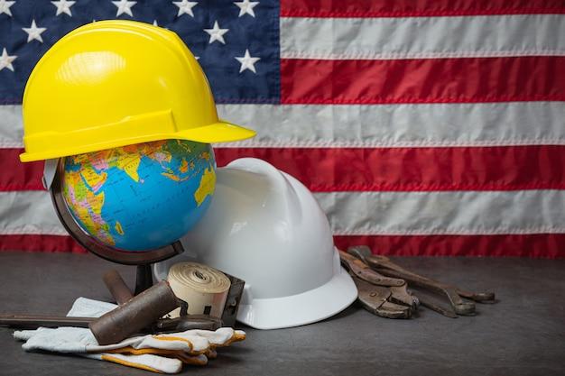 アメリカの国旗とヘルメット労働者の日のコンセプトに近いツール。 無料写真