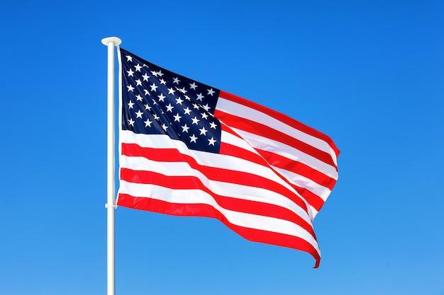 青い空に手を振るアメリカの国旗 無料写真