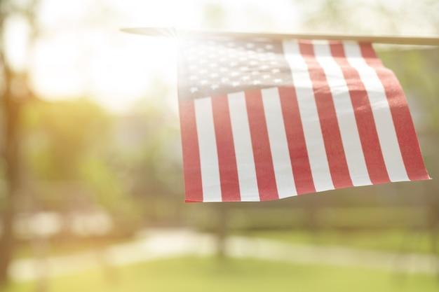 American flag with bokeh natural background and sunlight for