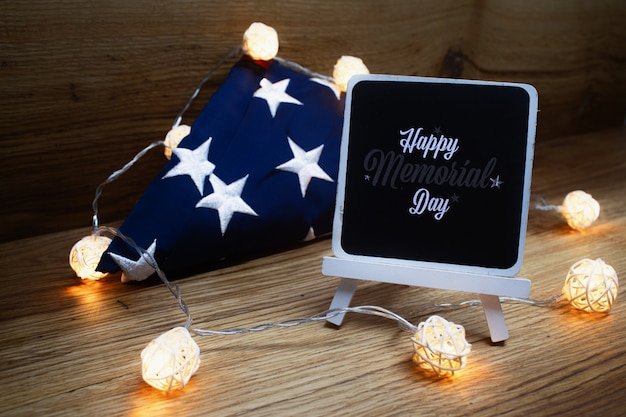 American flag with chalk board garland on a wooden background for memorial day. Premium Photo