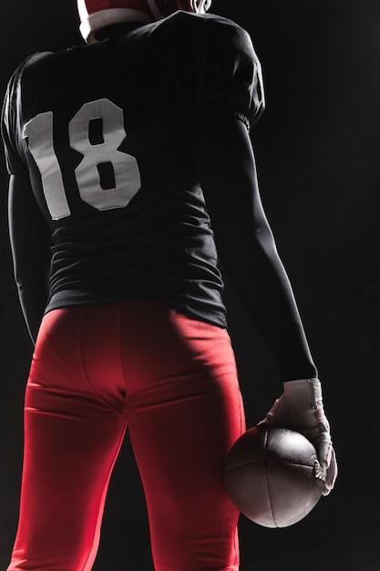 黒い背景にボールでポーズアメリカンフットボール選手 無料写真