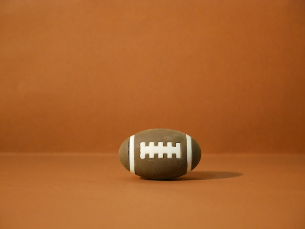 American football with copy space on brown background Premium Photo