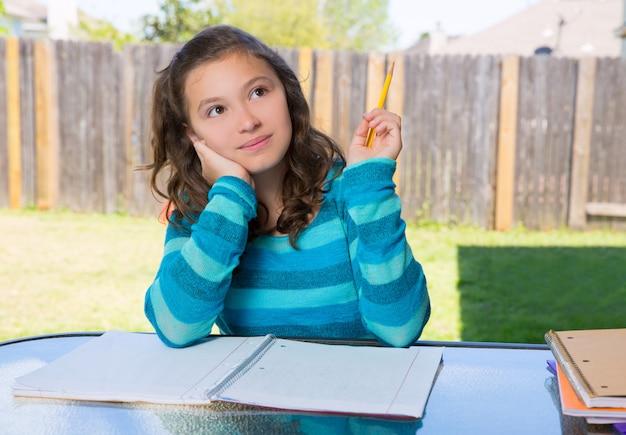 American latin teen girl doing homework on backyard Premium Photo