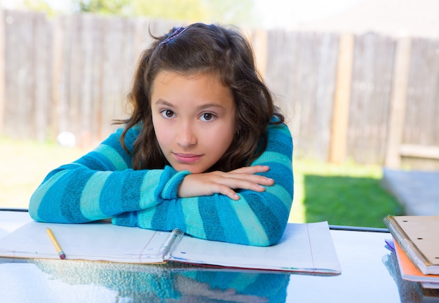 American latin teen girl doing homework on backyard Premium Photo