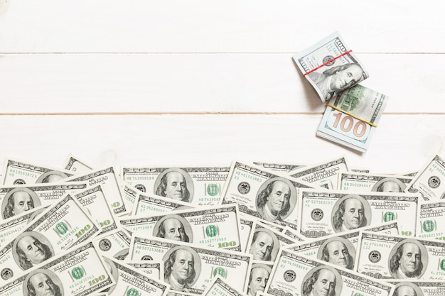 American money on colored background top view, with empty place for your text business money concept. one hundred dollar bills with stack of cash Premium Photo