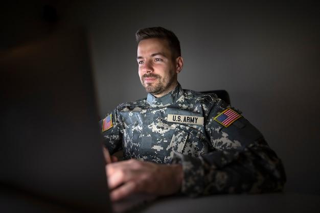 Soldato americano in uniforme militare con bandiere di patch usa che lavora fino a tardi sul computer Foto Gratuite