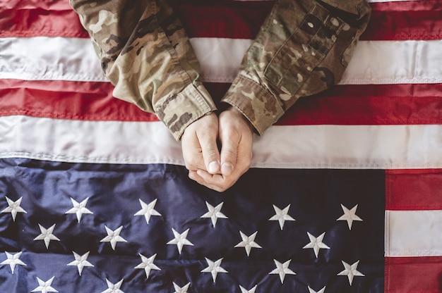 アメリカの兵士が彼の前にアメリカの国旗を悼んで祈っています 無料写真