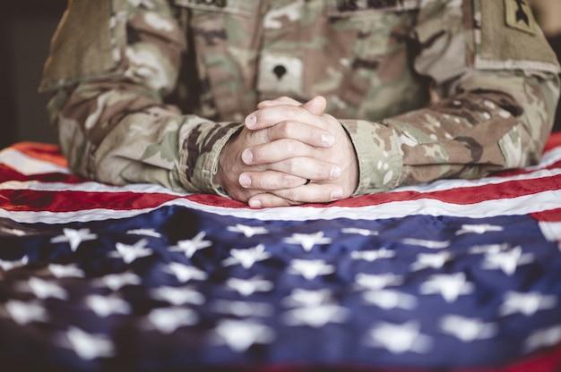 彼の前にアメリカの国旗を悼んで祈るアメリカ兵 無料写真