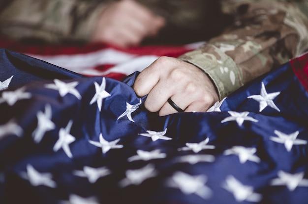 Американский солдат скорбит и молится с американским флагом перед ним Бесплатные Фотографии