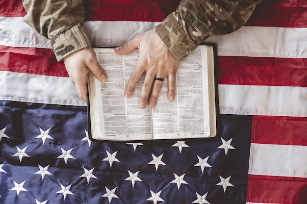 聖書とアメリカの国旗を手に、喪に服して祈るアメリカ兵 無料写真