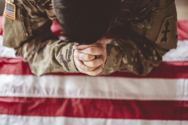 Soldato americano in lutto e in preghiera con la bandiera americana davanti Foto Gratuite