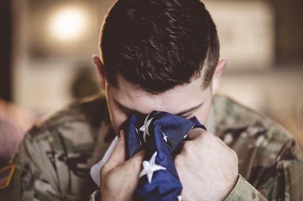 Soldato americano in lutto e in preghiera con la bandiera americana nelle sue mani Foto Gratuite