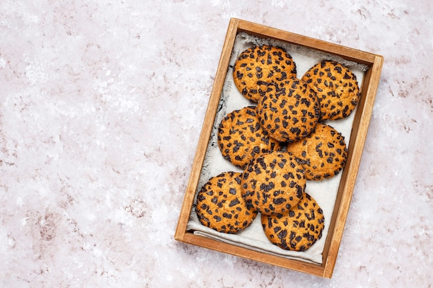 American style chocolate chip cookies in wooden tray on light concrete background. Free Photo