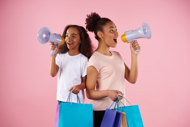 American woman and little girl are broadcasting in megaphone Premium Photo