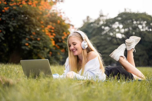 American women sitting with smiling happies and listening the music in the park for relax lifestyle Premium Photo