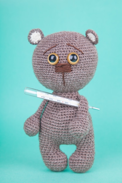 Amigurumi. diy toy. knitted brown bear cub with a thermometer. , prevention of childhood diseases Premium Photo