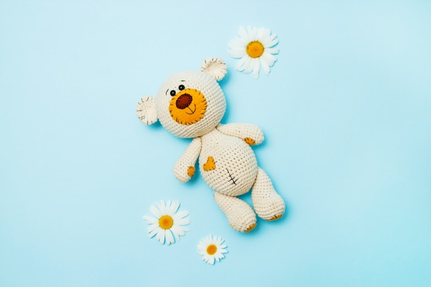 Amigurumi handmade teddy bear with daisies isolated on a blue background. baby background. copy space, top view. Premium Photo