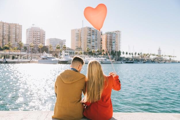 Amorous couple with balloon on romantic embankment Free Photo