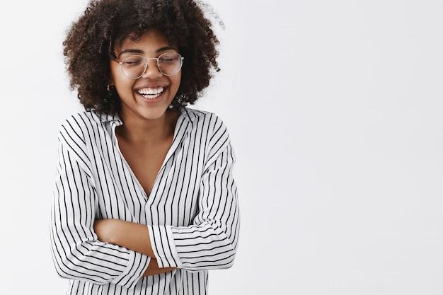 Веселая и беззаботная привлекательная афроамериканка в полосатой блузке и очках, закрывая глаза, громко смеется и держится за руки на груди, закрывая глаза, веселится Бесплатные Фотографии