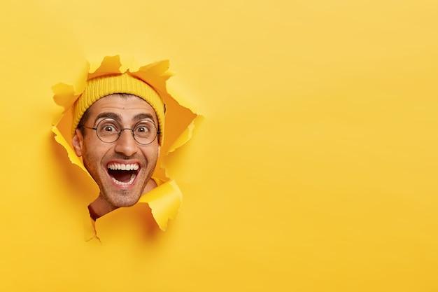 Забавный веселый молодой человек смотрит сквозь рваную дырку в бумаге Бесплатные Фотографии
