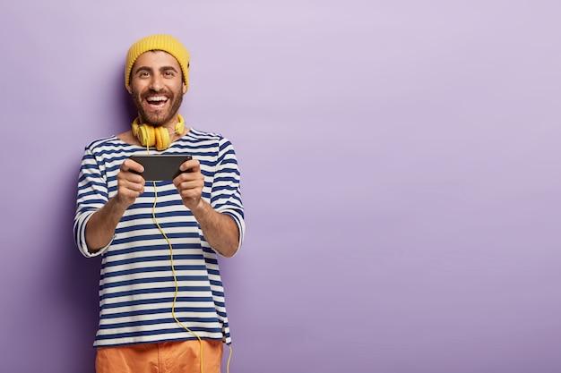 즐겁게 웃으며 휴대 전화로 비디오 게임을하고, 캐주얼 한 옷을 입고, 긍정적으로 웃으며, 목에 헤드폰을 착용 무료 사진