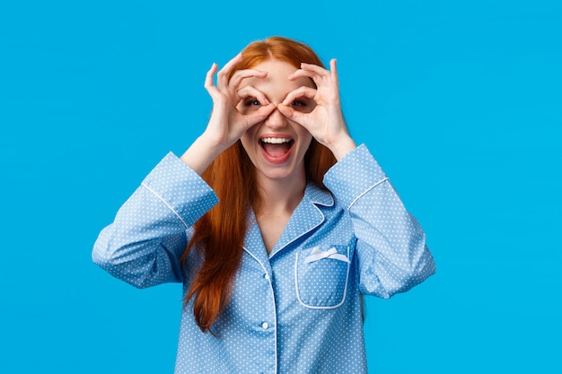 Amused girl seeing wonderful promo, want try out. attractive redhead woman in lovely pyjama make glasses with fingers, looking through smiling thrilled and excited, standing in nightwear Premium Photo