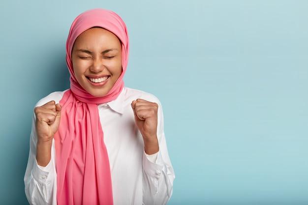 Веселая счастливая арабская женщина поднимает сжатые кулаки, успешно достигает цели, держит глаза закрытыми Бесплатные Фотографии