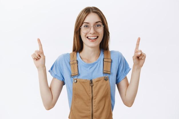Bella ragazza divertita e interessata con gli occhiali che punta il dito verso una buona offerta promozionale Foto Gratuite