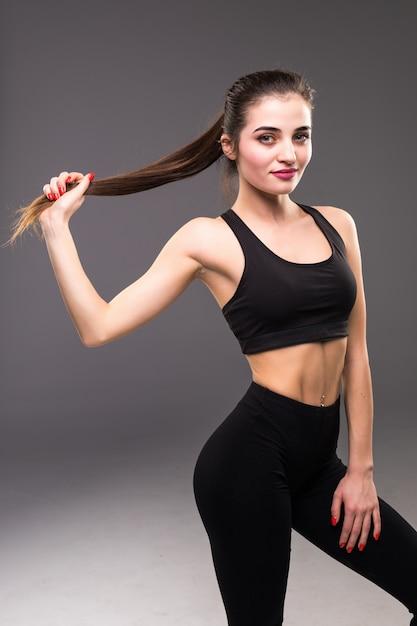 白い壁にポニーテールで彼女の長い髪を保持している陽気なフィットネス女の子を面白い 無料写真