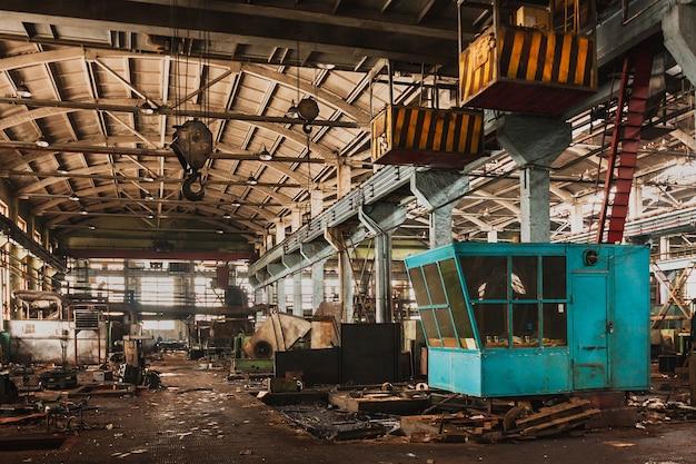 버려진 오래된 대형 산업 홀은 산업용 크레인 철거를 기다리고 있습니다. 프리미엄 사진