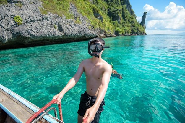 タイの伝統的なロングテールボートでアクティブな男はシュノーケリングとダイビングの準備ができて、ピピ島、タイ Premium写真