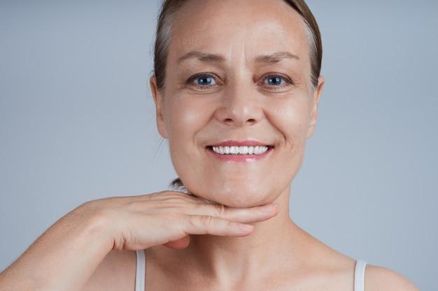 大人の笑顔の女性が手のひらであごに触れ、リフティングエフェクトクリームを塗ります。 Premium写真