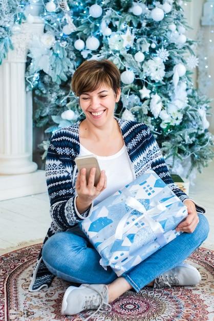 성인 여성이 그녀의 손에 전화로 크리스마스 트리 근처에 앉아 프리미엄 사진