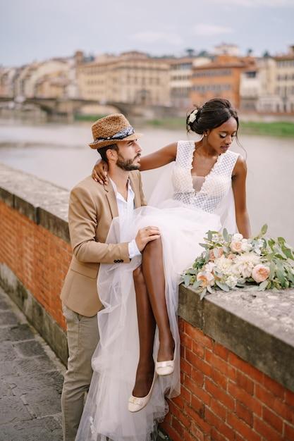 アフリカ系アメリカ人の花嫁がレンガの壁に座って、白人の新郎が彼女を抱擁します。街と橋を見下ろすアルノ川の堤防。異人種の結婚式のカップル Premium写真