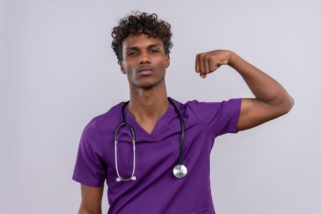 Агрессивный молодой красивый темнокожий доктор с кудрявыми волосами в фиолетовой форме со стетоскопом, поднимающим сжатый кулак Бесплатные Фотографии
