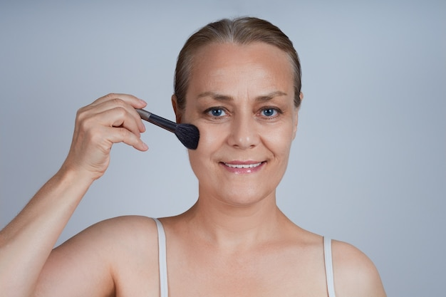 年配の女性が頬に装飾化粧品をつけています。高齢者の顔のスキンケア。 Premium写真