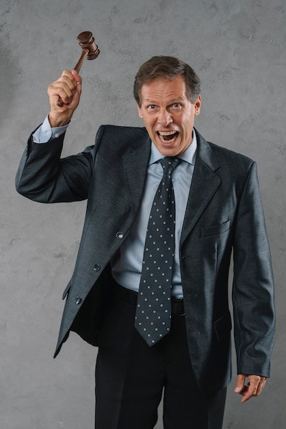 Злобный зрелый мужчина-юрист, ударяющий молотком по серому текстурированному фону Бесплатные Фотографии