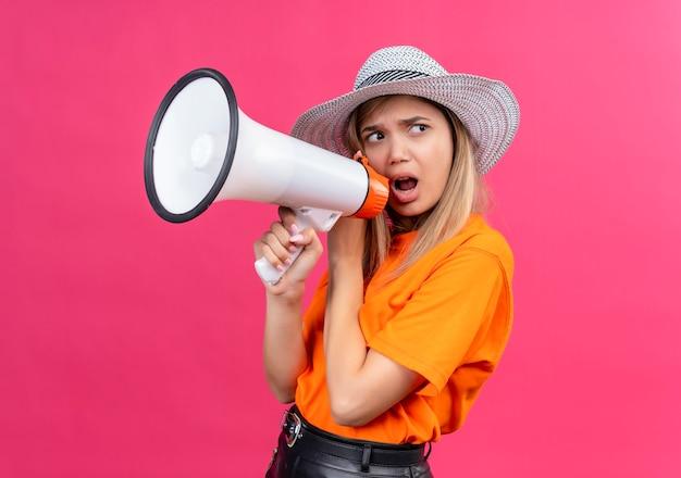 Злая симпатичная молодая женщина в оранжевой футболке в шляпе от солнца разговаривает через мегафон Бесплатные Фотографии