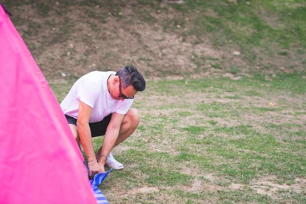 Азиатский мужчина в белой футболке устанавливает розовую палатку у кемпинга Premium Фотографии