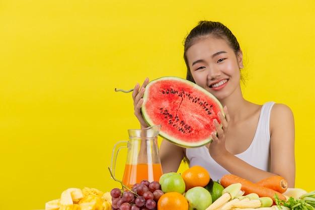 白いタンクトップを着ているアジアの女性。両手はスイカを持っており、テーブルにはさまざまな果物がいっぱいです。 無料写真