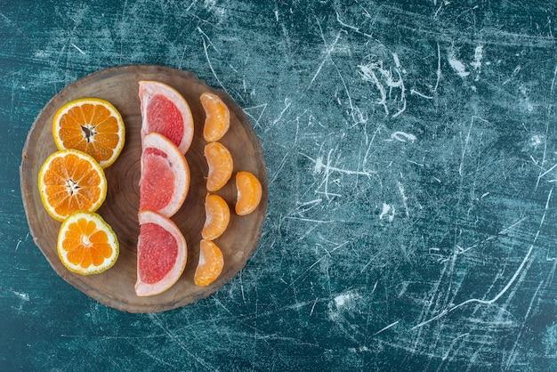 青い背景の上のボード上の柑橘系の果物のスライスの品揃え。高品質の写真 無料写真