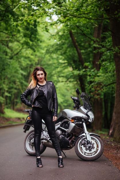 Привлекательная сексуальная девушка, одетая в кожу, позирует возле спортивного мотоцикла на улице Бесплатные Фотографии