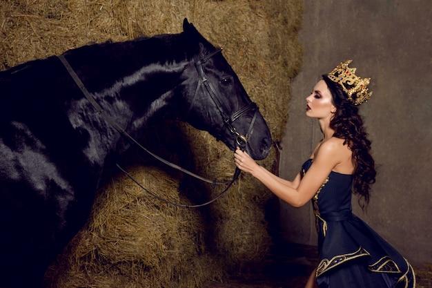 黒い馬を見ている冠を持つ魅力的な女性 Premium写真